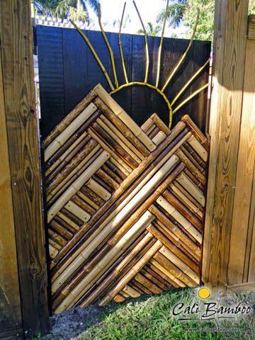 Random bamboo pole scraps used to create outdoor artwork on a garden gate.