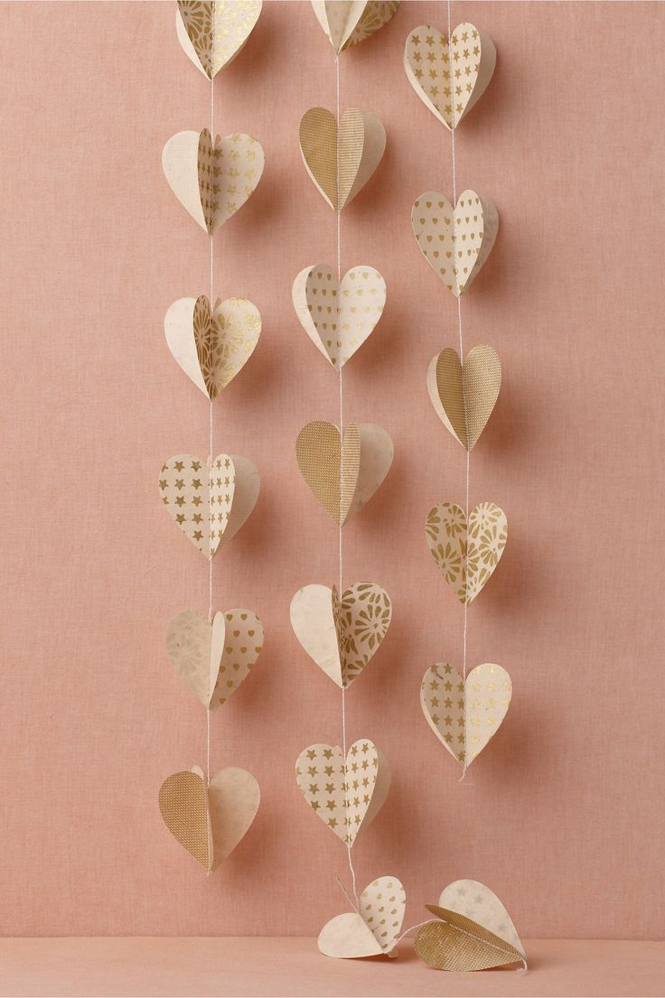 Heart of gold garland by BHLDN  Handcrafted in Nepal from sustainable Lokta paper, these three-dimensional 96-inch strands of ivory and gold gilded 3-inch hearts are the perfect accent to any love-filled occasion. Set of 3. $22