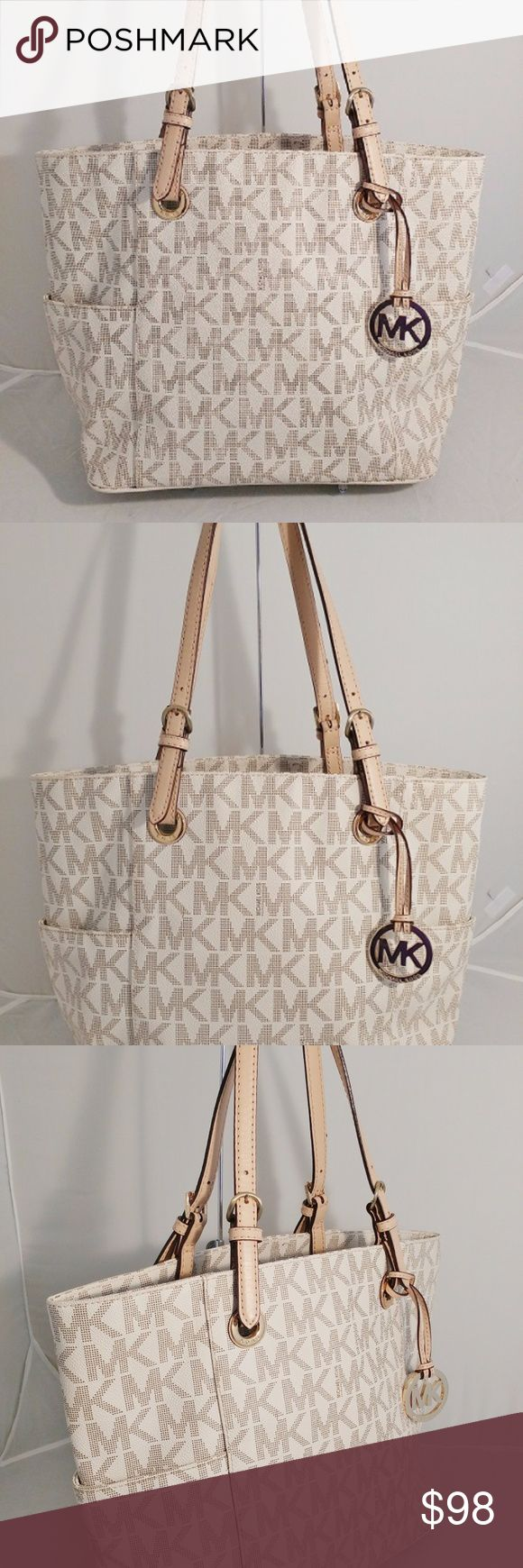 """Michael Kors East West Signature Vanilla Tote Bag Expert-level organization and glamorous details make this MICHAEL Michael Kors Jet Set tote the ultimate work-play-travel companion. Faux leather Large sized bag; 14-1/2""""W x 10-1/2""""H x 5-1/2""""D Silhouette is based off 5'9"""" model 8""""L double handles Open top 2 exterior side slip pockets 1 center zip interior compartment, 4 slip pockets & key clip Michael Kors Bags Totes"""