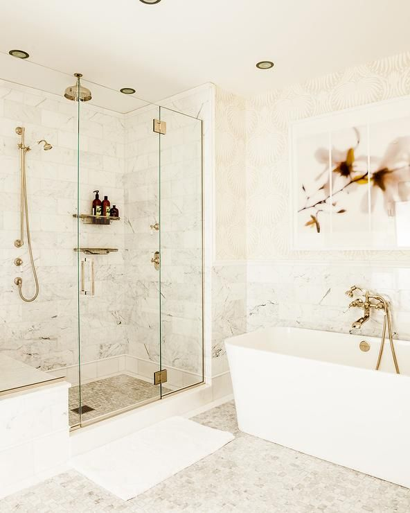 Gorgeous beige and white bathroom is equipped with a freestanding bathtub placed on geometric marble floor tiles beneath a triptych art piece mounted on a wall covered in Farrow & Ball Lotus Wallpaper lined with marble lower wall tiles.