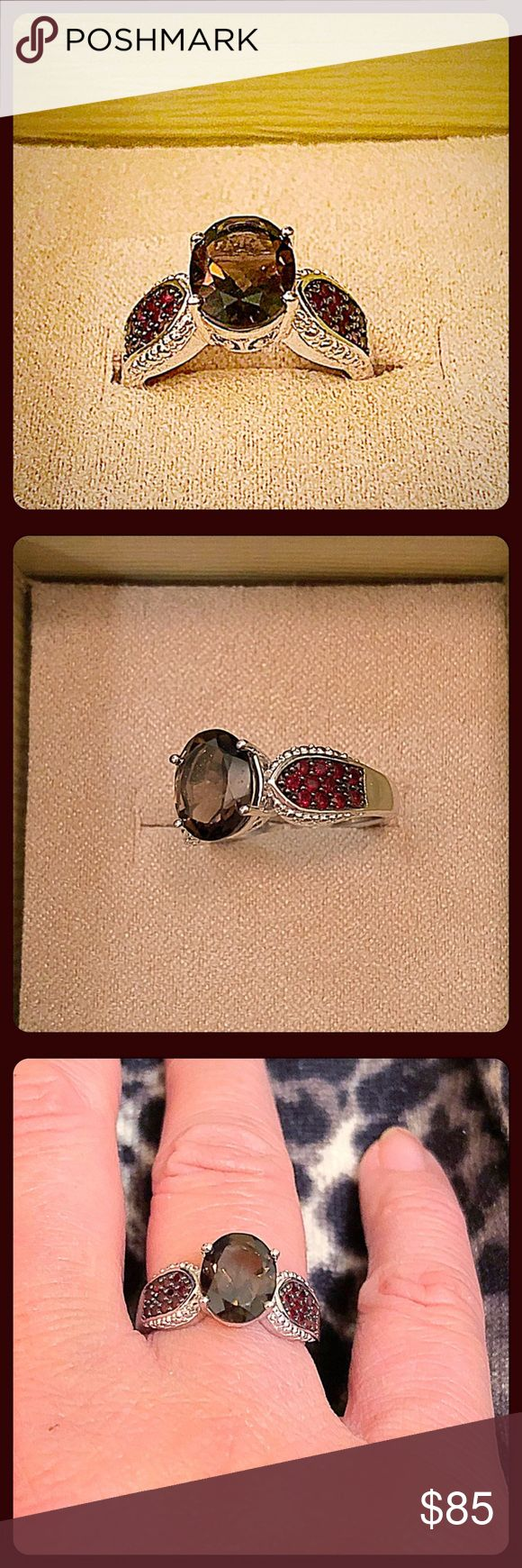 ✨Gorgeous .925 SS Smoky Quartz & Garnet Ring✨ This is a really pretty ring in person. The center prong set stone is a nice saturated smoky quartz which is 1.95ct. or an 8x10mm size stone. Each side has a total of about .35ct of round pave derp red garnet stones. Intricate carvings on the sides. The .925 sterling silver is rhodium overlayed to minimize tarnishing. 5g total wt. Great as a gift or for yourself😉 NWT Size 7. Thai Artisans Jewelry Rings