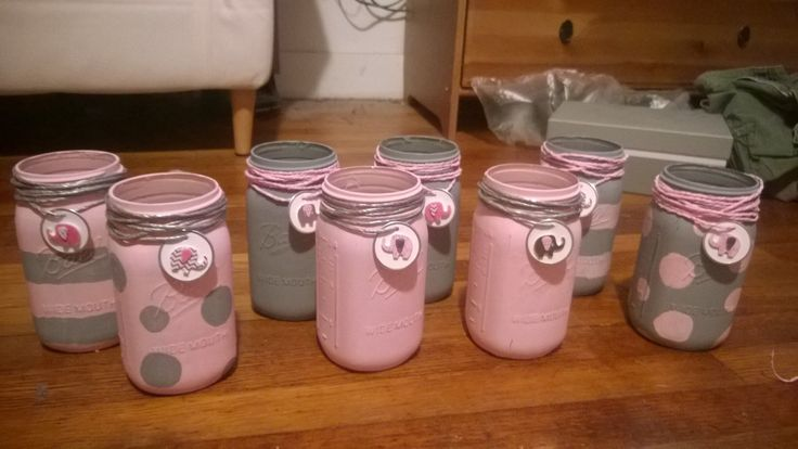 Table Centerpieces: Large painted pink and gray mason jars with mutli cute designs for flowers to be filled with, pink and gray paper rope wrapped around top with little elephant sticker decorations to bring in the elephant theme for your centerpiece. These can be requested and made to order through Etsy on VioletsByTheSea page.The sellers contact name is Megan Spieler ! ---- https://www.etsy.com/shop/VioletsByTheSea?ref=l2-shop-header-avatar