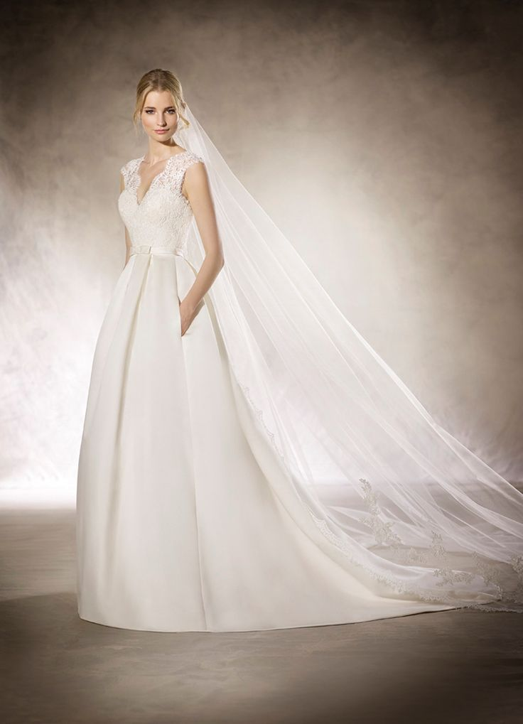 HYRIA - Delicate princess wedding dress in real satin. A full skirt complements a tulle bodice with guipure appliqué and gemstones that culminate in a V-neckline.