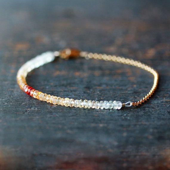 LIMITIERTE AUFLAGE. Eine Schwung des wunderschönen Saphir Edelsteine in einem Spektrum von orange Farbtöne simuliert einen Ombre in den funkelnden Steinen. Ätherisch, weiße Saphire zu hellorange durch Feuer heiß Orange führen und wieder zurück. Auf weichen Perle-weiß flexibler Draht aufgereiht und gegenübergestellt mit einem 14 k gold gefüllt-Kette und Hummer-Verschluss, ist der Effekt, zart und schön. Gesamtlänge beträgt 7 Zoll. Das letzte Foto zeigt wie drei ähnliche Armbänder aussehen…