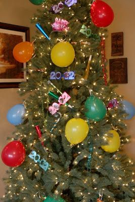 Strip the Christmas Tree down to white lights and transform it into a New Year's Eve Tree complete with hats and party horns...Great Idea