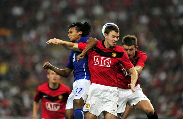 Jonny Evans (C) and Michael Carrick of Manchester United clash with Mohd Amri Yahyah of Malaysia XI during the pre-season friendly match between Manchester United and Malaysia XI at Bukit Jalil National Stadium on July 20, 2009 in Kuala Lumpur, Malaysia.