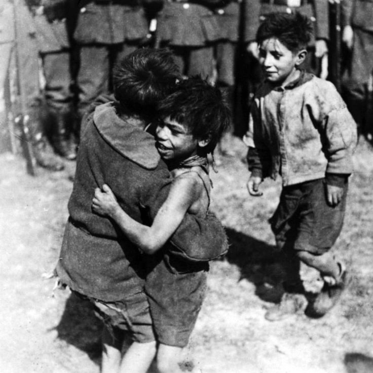 """Three little Roma (Gypsy) boys comfort one another in front of a unit of German soldiers. The location and date are unknown, possibly France or Poland. The image was most likely taken during a deportation round up to a concentration camp or ghetto. The genocide of Gypsies during the war is called the Porajmos, which means the """"devouring"""" or the """"destruction"""" in the Romani language. Unknown date and location (possibly France or Poland). Europe. Circa 1940-1944."""