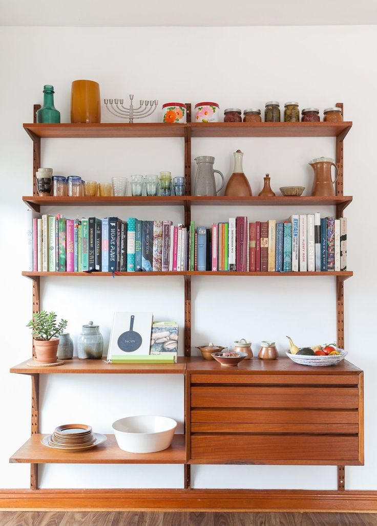 Midcentury Modern wall unit adorned with books and vintage ceramics collected over time.