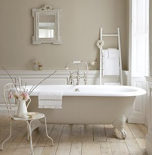 White victorian bath, wood flooring, panel & edge molding, ladder towl rack, & metal-white chair as a planter table. Clean, relaxing & simple interior design.