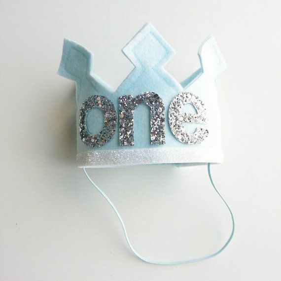 First Birthday Felt Crown Shown in first pic with ice blue felt and white glitter trim and silver Metallic glitter letters. .ready to ship in this color Measures approximately 3 3/4 High by 4 in diameter Perfect Crown for a boy or girl Crown can be customized in many different colors. .please check our section under party hats and crowns to customize your own.