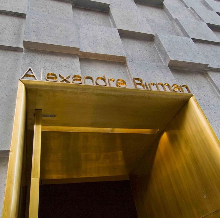 Alexandre Birman Store   travertino nero marble   moldura curva em latão envelhecido   old brass