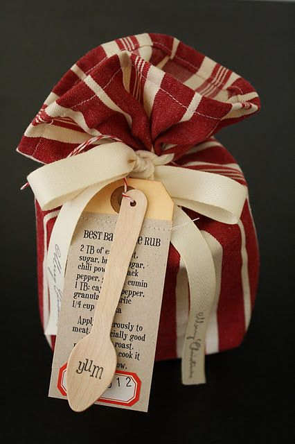 A simple homemade gift wrapped up in a holiday dish towel and a terrific tag and a recipe tag with a stamped spoon.