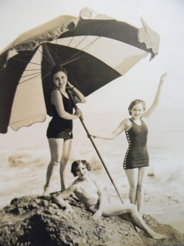 These are were featured players in the 1920′s at Universal Pictures back in the silent movie days. Under the parasol is Barbara Kent, standing beside her is Barbara Worth, and reclining at their feet is Ethlyne Clair.