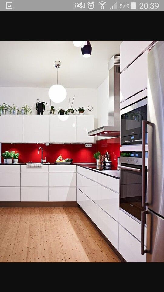 minimalist white kitchen with red backsplash 28