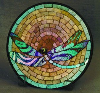 This is a trivet and a whimsey. A trivet is a device in which you put something hot on, until it cools. A whimsey is a piece made by a craftsman, and taken home for his personal use. The maker of this piece, Edwin Hayward, was a worker at Tiffany Studios.
