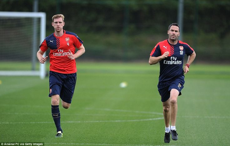 Arsenal centre back Per Mertesacker also jogs alongside fitness coach Forsythe as he looks...