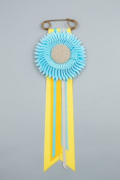 Light blue with yellow, light blue, dark yellow & light blue cotton tails. Natural linen centre. Vintage safety pin.