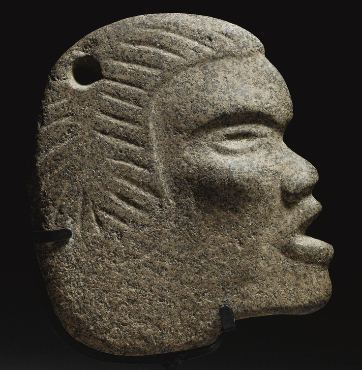 A MAYA STONE HACHA,  LATE CLASSIC, CA. A.D. 550-950  the finely carved human head of slender section, with prominent youthful cheekbones, small upturned nose and open mouth, with distinctive striated coiffure, in speckled grey and brown basalt, pierced at the top.  height 8 3/4 in. 22.2 cm