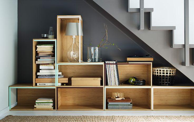 Stacked arrangement of IKEA storage boxes under a stairway.