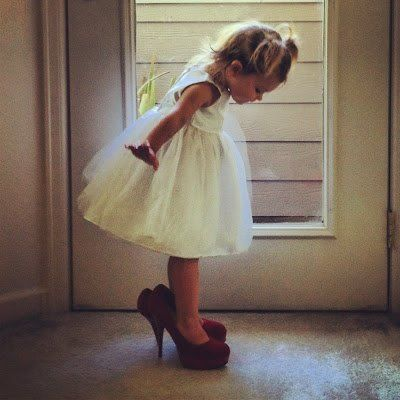 Cute picture of flower girl in the bride's shoes.