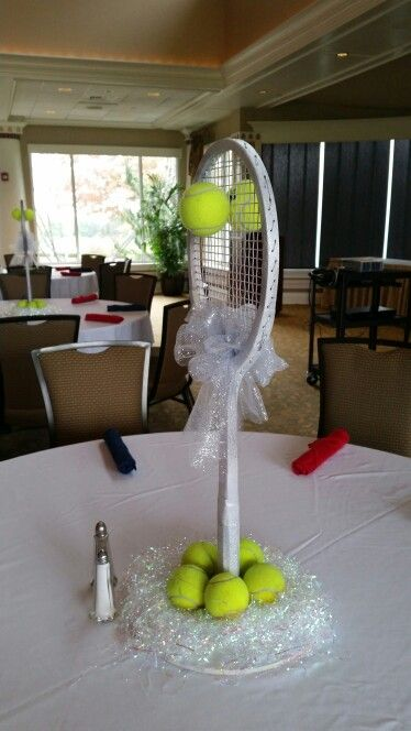 Repurposed wooden tennis racquets for tennis banquet centerpieces. [Racquet is secured to round wooden base]
