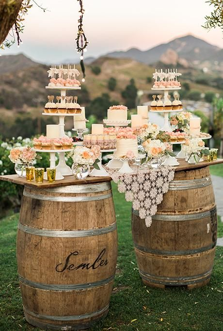 A pink-and-cream dessert bar on wooden barrels featuring miniature cakes and cupcakes | Brides.com