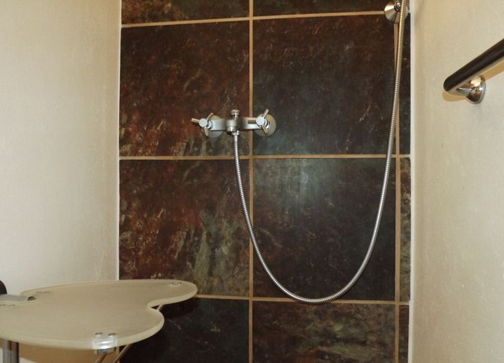 Wheelchair friendly shower, showing fold up/down seat, grab rail and additional hand held shower.