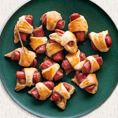 Pigs in a Blanket  2 tablespoon(s) butter  1 large yellow onion, thinly sliced  1/2 teaspoon(s) kosher salt  1/4 teaspoon(s) black pepper  1 egg     1 (9-by-9-inch piece) frozen all-butter puff pastry dough, thawed but still very cold  4 (5-inch) pork hot dogs or beef hot dogs  Chinese hot mustard, or other favorite mustard, for dipping