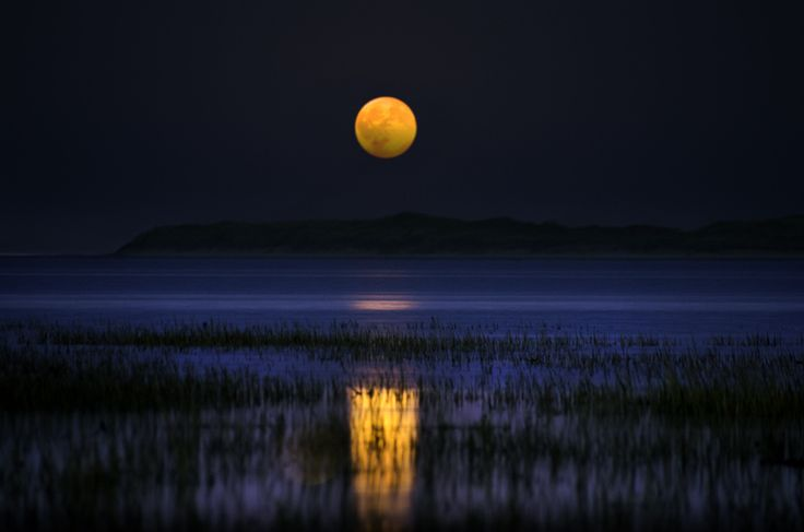a waning Gibbous of a fat moon illuminating the causeway at Holy Island.  By Karen Atkinson.
