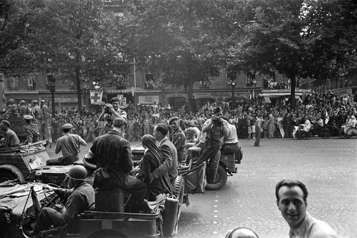Allied troops and journalists — including photographers Robert Capa (on the back of a Jeep with a camera in front of his face) and George Rodger (with camera, wearing a beret) who helped found the great Magnum collective — in the streets of Paris during the city's liberation, August 1944.    Ralph Morse - LIFE