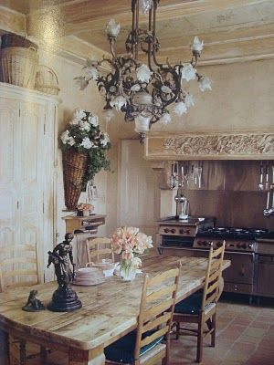 French kitchen with farmhouse table and ladder back chairs. Beautiful stove as well!