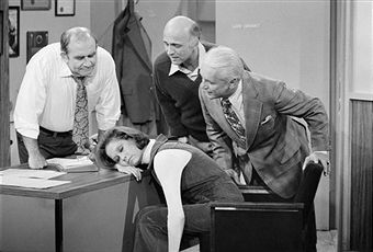 American actress Mary Tyler Moore (as Mary Richards) sleeps on a desk in a scene from the 'Mary's Insomnia' episode of 'The Mary Tyler Moore Show' (also known as 'Mary Tyler Moore'), Los Angeles, California, September 17, 1976. Gathered around her are, fron left, fellow actors Ed Asner (as Lou Grant, on whose desk Mary sleeps), Gavin MacLeod (as Murray Slaughter), and Ted Knight (1923 - 1986) (as Ted Baxter). The episode originally aired on December 4, 1976