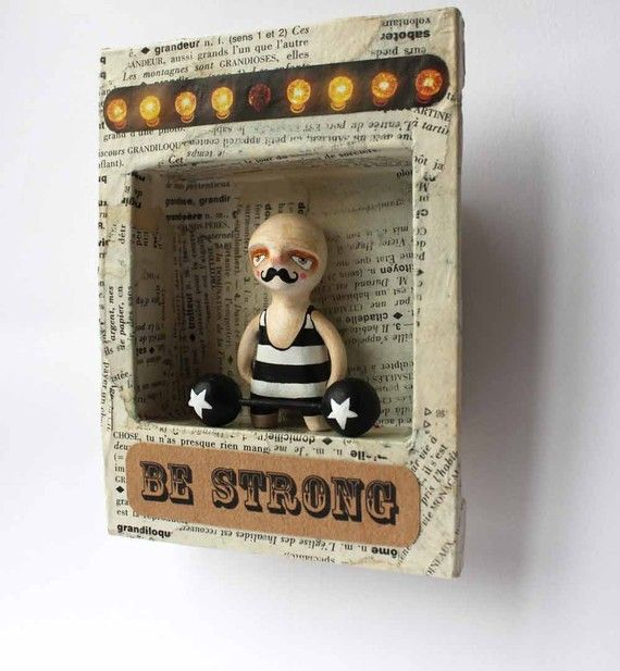 Serguei is a Russian weightlifter who after much roaming ended up working in a Parisian circus. The papier-mache box, made from and old French dictionary, is about 6x4 inches. Serguei is hand-sculpted in air drying clay, painted with acrylics and vanish. He is about 2 inches tall.