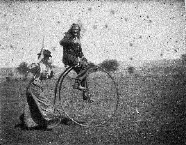 Man on a penny-farthing bicycle being chased by his sister (Maggie & Bob Spiers) - West Wyalong, NSW, C. 1900.  Find more detailed information about this photograph: http://acms.sl.nsw.gov.au/item/itemDetailPaged.aspx?itemID=390869  From the collection of the State Library of New South Wales www.sl.nsw.gov.au