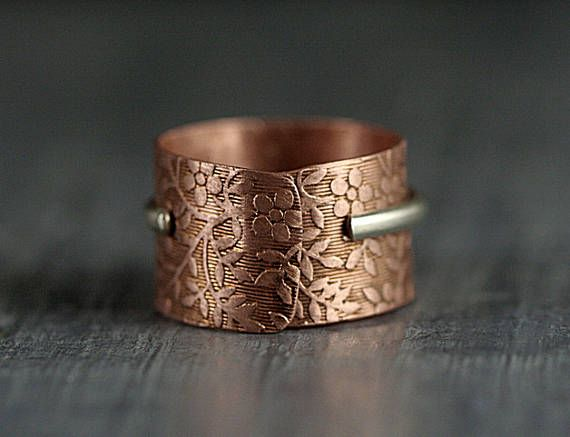 Unique bicolor ring made of copper and sterling silver. The wide band ring with floral pattern is made of copper. The stacked thinner one is 925 sterling silver with a light blue zirconia stone. The ring is adjustable to any measurement, so it can e.g. be worn alternatively on different fingers. It makes a perfect gift to a beloved person. All my items are safely and nicely packed in elegant Villa Sorgenfrei gift boxes. Item ships from Berlin, Germany, Europe with registered mail. Shipmen...