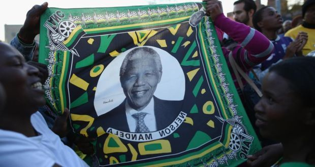 Supporters of former South African president Nelson Mandela hold a flag depicting the former South African leader as they wait to hear news of his condition outside the Heart Hospital where Mandela is being treated for a lung infection. Photograph: Getty Images
