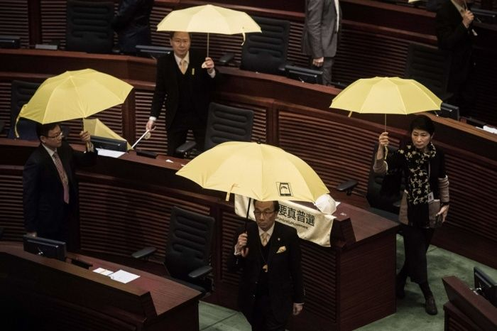 Pro-democracy members of the Hong Kong legislative council walk out in protest before Hong Kong leader Leung Chun-ying's policy speech. Leung took a hard line warning pro-democracy protesters that they risk sparking anarchy, as he sought to bolster his support in his first policy address since demonstrations rocked the financial hub last year.