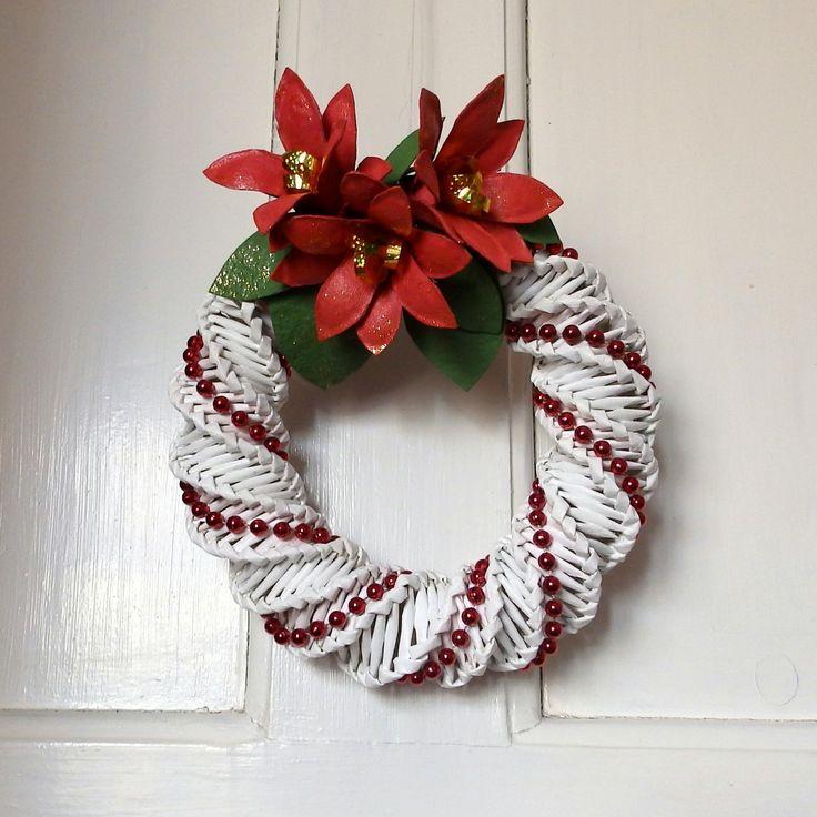 Věneček s vánoční hvězdou Bílý dekorační věnec vyrobený z papírového pedigu, ozdobený červenou perličkovou šňůrou ačervenými vánočními hvězdami se zelenými listy. Na dveřích vykouzlí tu správnoju adventní atmoféru. Doporučuji zavěsit někam, kde neprší. Průměr věnečku je 21 cm.