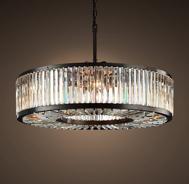 """WELLES CLEAR CRYSTAL ROUND CHANDELIER  The geometric design of our lighting collection echoes the luxurious lines of Art Deco, a style born in 1920s Paris. Framed in welded raw iron, it's clad with close-set, optical-quality prisms that reflect the light and create endlessly shifting sparkle.  DIMENSIONS Overall: 43½"""" diam., 15¾""""H Chain: 24""""L Weight: 218.3 lbs.  In store now."""