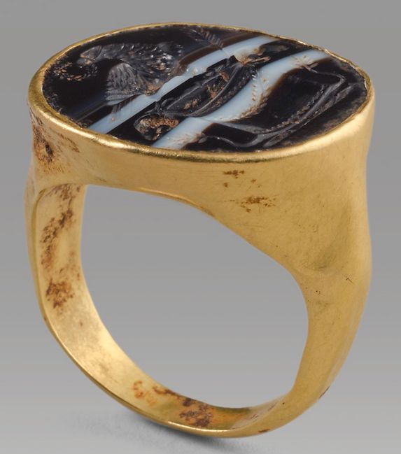 Gold and Banded Onyx Ring Depicting the Eagle of Rome, 1st Century ADThis ring is a particularly fine example of a form known across the Roman empire. The black-and-white banded onyx intaglio depicts the eagle of Jupiter with a wreath in its beak on a pyxis with ram heads each side and ears of corn below. The gem is elegantly accommodated into the gold bezel which rounds in perfect geometry at each end. Effectively a continuity of propaganda from the First Triumvirate (Caesar, Pompey, and…