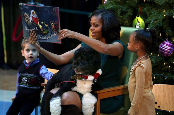 Michelle Obama Photos - First Lady Michelle Obama reads a Chritmas story while her dog Bo sits on her lap and 5-year-old AJ Murray (L), and 5-year-old Jordyn Akyoko sit nearby at Children's National Medical Center on December 14, 2012 in Washington, DC. The first lady toured the hospital before greeting 200 patients and hospital staff. - Michelle Obama Photos - 3973 of 9409