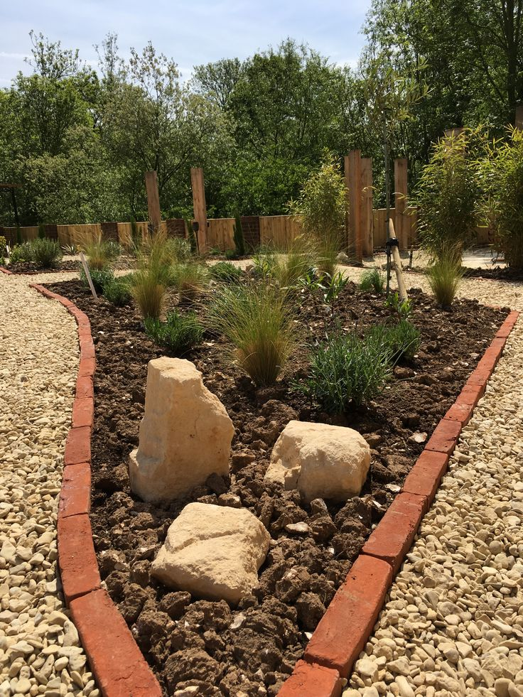 Terracotta brick edging, cotswold boulders and prairie style planting