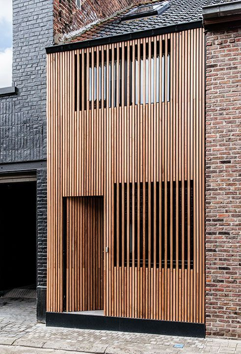 The architectural wooden house brings serenity to the brick surroundings.: