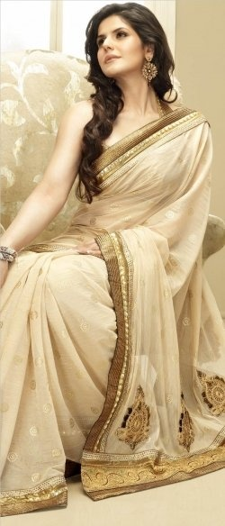 Zarine Khan in beautiful cream designer georgette saree with polka dots all over saree and zari work border and patch work paired with designer sleeveless saree blouse. #zarine #khan