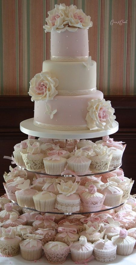 Wedding cake with cupcakes on the bottom stand.