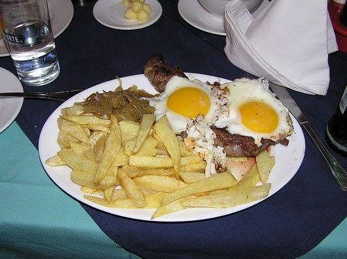 Bistec a lo pobre. Beefsteak, french fries, fried onions, covered with a couple of fried eggs.