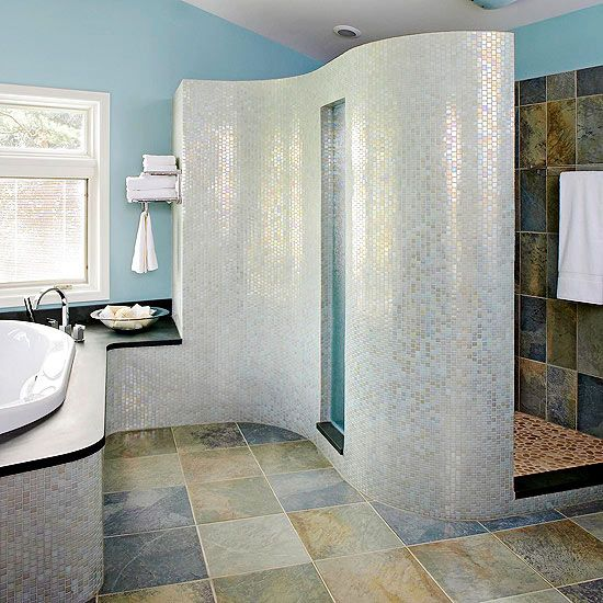 Curved Shower Wall - An S-shape wall on one side of this shower references the flow of waves and serves as a stunning focal point for the bathroom. Covered in shimmering glass tiles, the wall features a glass panel in the center to admit light into the shower. With a low curb, extra-wide entrance, bench, and handheld showerhead, this stylish shower is easily accessible for everyone.