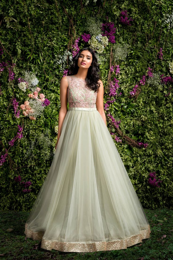 A Subdued Green gown with a tulle flare and fitted bodice .The bodice has gold pita embroidery outline with hint of pink.The bias flare is finished with heavy sequenced embellishment.