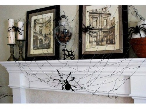 mantel decorations: love the spiderweb and the glass vase filled with black potpourri