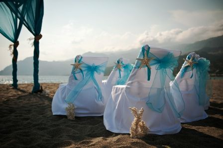 Beautifully dressed chairs with bows & starfish for beach wedding in Crete by Moments.